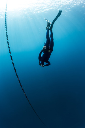 deepsea: The underwater scenes. Scuba diver swims under water with chain