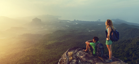 Couple of hikers with backpacks watching sunrise with valley view Archivio Fotografico