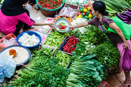 top seller: The purchaser takes the product from the seller at the vegetable market
