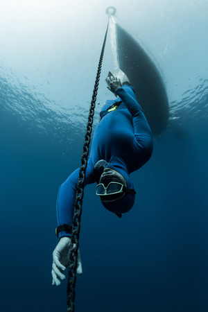 descending: Free diver descending along the metal chain using his hands (free immersion)