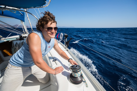 skipper: Young sailor on the yacht working with rope on the winch