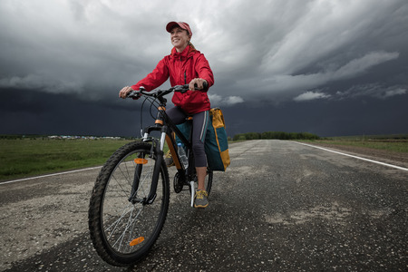 empedrado: Lady hiker riding loaded bicycle on the paved asphalt road with stormy clouds on the background