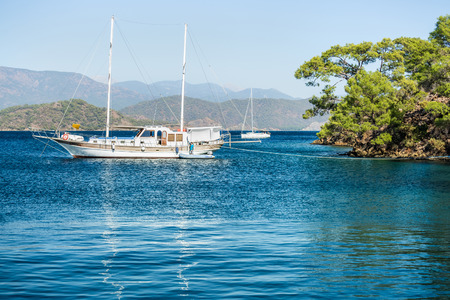oludeniz: Calm bay with clear water and ancored sail boat. Skopea Limani, Turkey Stock Photo