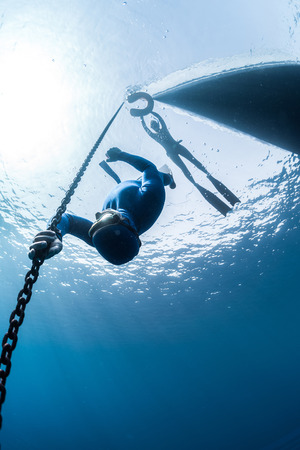 deepsea: The underwater scenes. Two scuba divers swim under the water at the chain