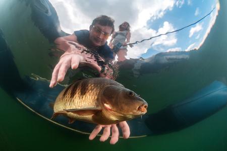 transparente: Las escenas bajo el agua. Pescador en un barco captura un pez bajo el agua