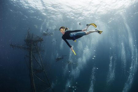 free diver: Free diver on depth with ship wreck on the background