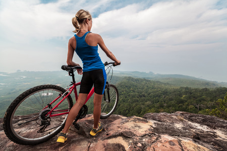 Young lady with bicycle standing on the top of mountain with view valley