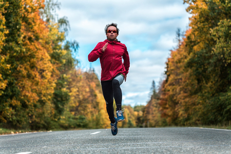 sports uniform: Man in a sports uniform and glasses running down the road in the autumn forest Stock Photo