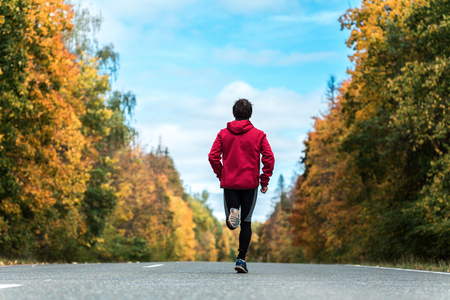 sports uniform: Man in a sports uniform running down the road in the autumn forest