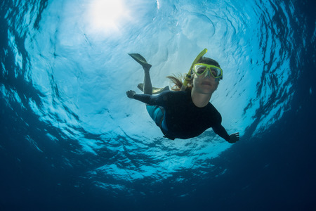 deep: Close up underwater shot of the lady freediver in yellow mask