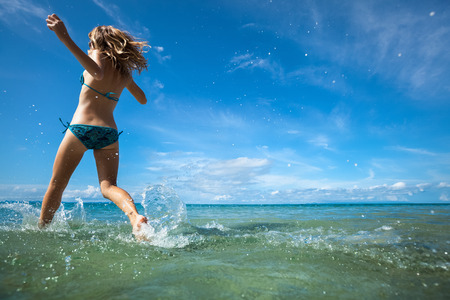 girls naked: Young woman running into sea