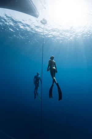 picada: Dos buceadores que ascienden desde la profundidad usando aletas. disciplina peso constante