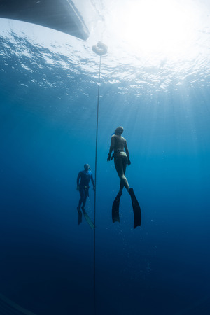 freediving: Two freedivers ascending from the depth using fins. Constant weight discipline