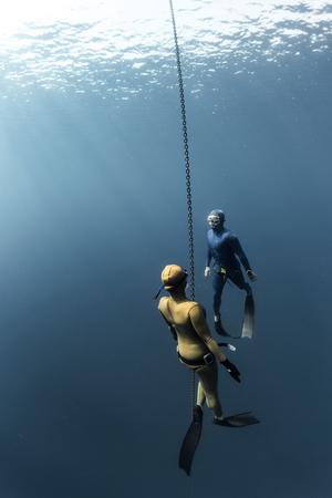 水中のシーン。2 つのスキューバダイバーは、チェーンを使用して水の下で泳ぐ