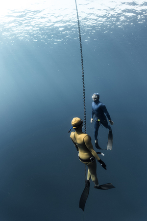 deepsea: The underwater scenes. Two scuba divers swim under the water using chain Stock Photo
