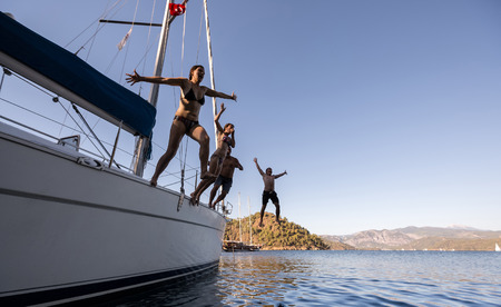 starboard: Group of young friends jumping from the yacht into sea Stock Photo