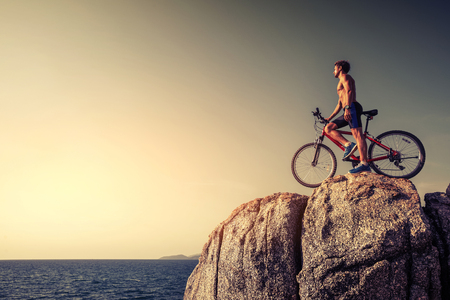 cliff edge: Man standing with a bicycle on the rock during sunset