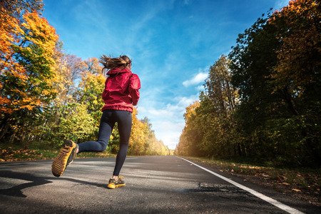 Lady in sportswear running along the road in the autumn forest Stock Photo