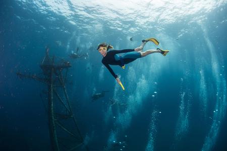 수중 장면. 레이디 다이버가 침몰 한 배에서 물속으로 수영한다.