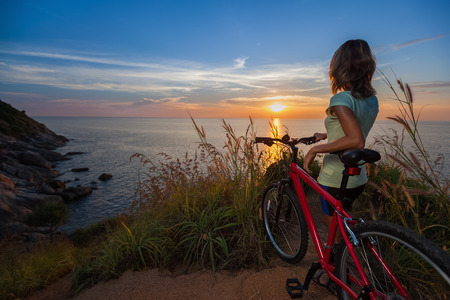 over the hill: Young lady standing on top of a hill with bicycle and enjoying the sunset over sea Stock Photo