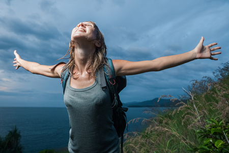 Tourist with backpack and wet clothing standing with raised hands with dark sky on the background Stock Photo