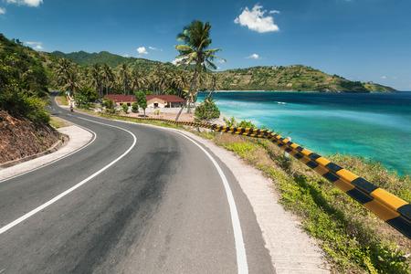 coastlines: Asphalt road along a tropical sea coastline leading through villages and forests