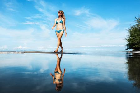 Lady walking alone on the sandy tropical beach