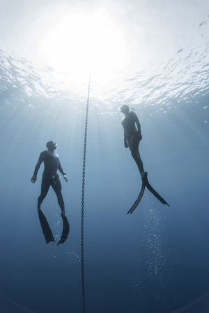 freediver: Two freedivers ascending from the depth using fins. Constant weight discipline