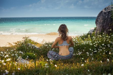 yoga pants: Lady sitting on the grass near ocean and doing yoga exercise