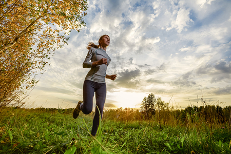 woman alone: Slim lady running in the autumn forest