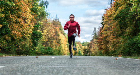 Man in a sports uniform and glasses running down the road in the autumn forest Imagens