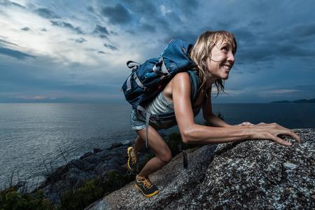 Caminante con la mochila de escalada de pared rocosa natural en el fondo nublado oscuro. Hay gotas de agua en la piel