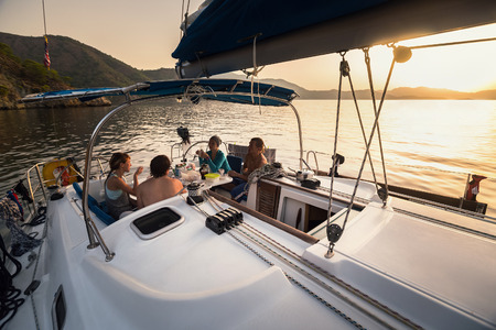 Group of young people have a dinner in anchored yacht during sunset Imagens - 59291210