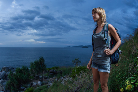 Portrait eines weiblichen Wanderer mit Rucksack und nasse Kleidung auf einem dunklen Hintergrund des bewölkten Himmels