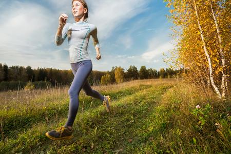 Schlanke Dame im Herbstwald läuft
