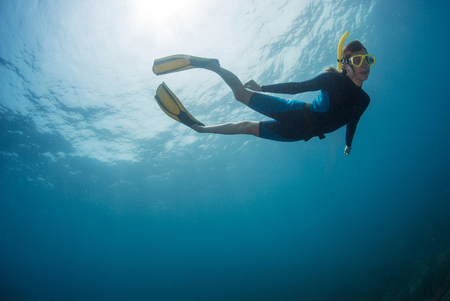 freediver: Close up underwater shot of the lady freediver in yellow mask