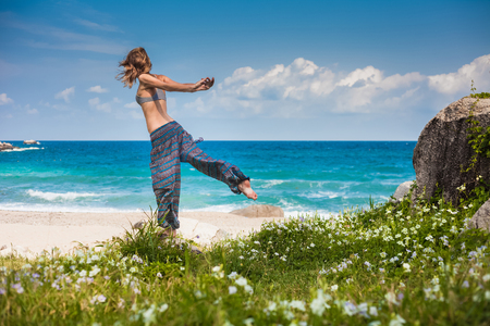 blue sea: Lady stretching on the sandy beach near blue ocean Stock Photo
