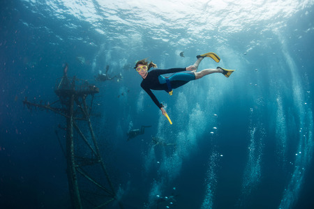 old ship: The underwater scenes. Lady the diver swims underwater from sunken ship