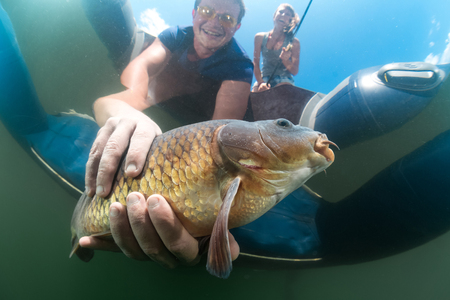 cyprinidae: Underwater view of the man catching the fish