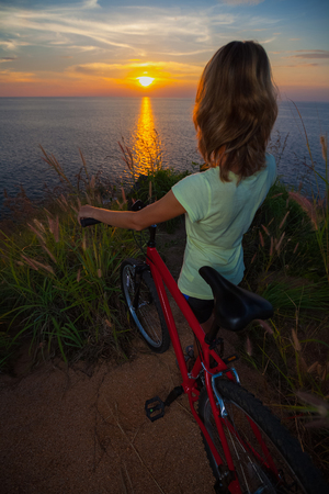 woman sunset: Young lady standing on top of a hill with bicycle and enjoying the sunset over sea Stock Photo