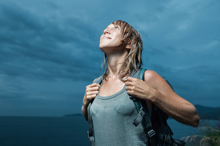 women smiling: Smiling tourist with backpack and wet clothing standing and looking to the dark sky