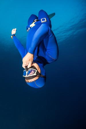 Freediver descending with monofin. Free immersion discipline Stock Photo