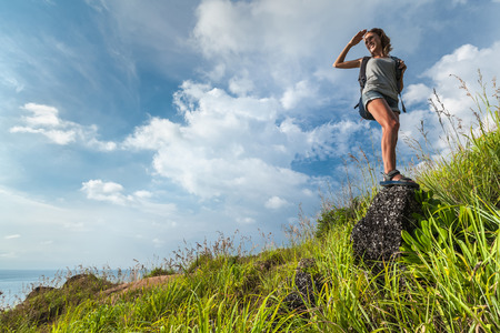 Lady hiker with backpack standing on the green meadow and enjoying sea view Stock Photo