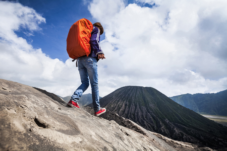 Backpacker walking on an edge of volcano crater