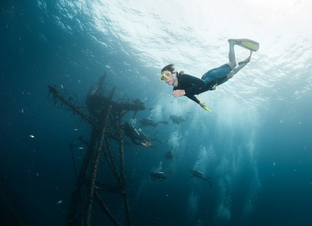 skin diving: Woman diving on a breath hold near the ship wreck Stock Photo