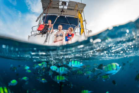 animal woman: Three girls feeding fish from a boat, split shot with underwater view