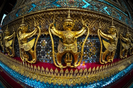 daemon: Wall of the temple with golden statues. Thailand