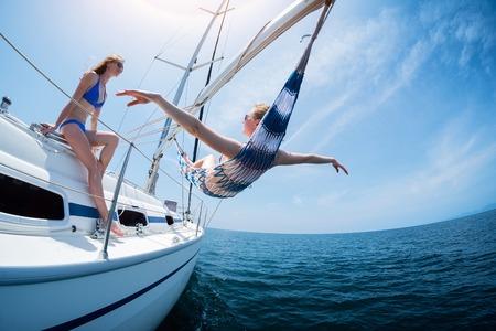 Deux femmes se détendre sur le bateau à voile se déplaçant dans la mer