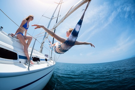 sail boat: Two women relax on the sail boat moving in the sea
