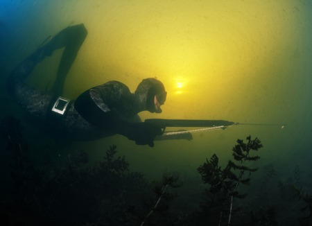 Underwater shot of the hunter with speargun in a lake with dirty water Stock Photo